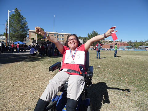 Sharing her ribbon at the Special Olympics, participating adult with disabilities.